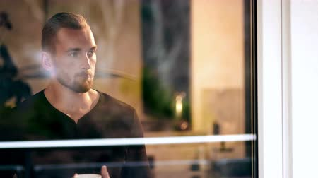 looking towards : Attractive blonde man wearing a black shirt, standing inside his home with a mug drinking. Looking out of his window, looking away from camera. Shot in 4K. Stock Footage