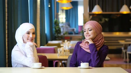 malajsky : two beautiful young Muslim women laughing and joking while sitting at a table in a cafe Dostupné videozáznamy