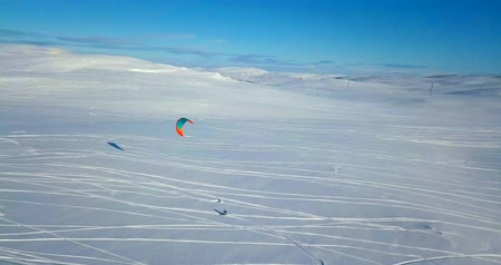snowboard : Aerial view of people snowkiting in tundra.