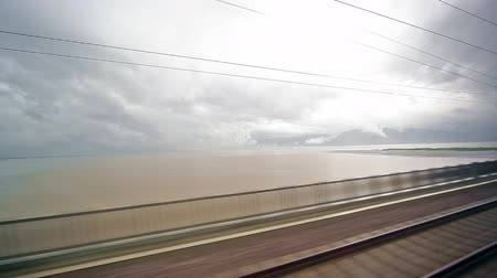 light : A view of the landscape from moving train passes over lake Stock Footage