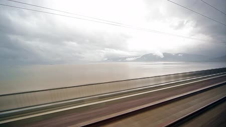 vasúti : A view of the landscape from moving train passes over lake Stock mozgókép