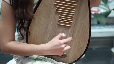 instrumentos : Chinese girl wearing a cheongsam playing the national instrument - pipa