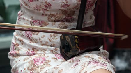 barbante : Chinese girl wearing a cheongsam playing the national instrument - Erhu Vídeos
