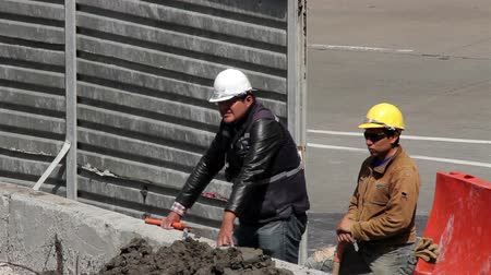 indústria : Mexico City, Mexico-August 2014: Two construction workers resting a moment. Nowadays the construction business is decreasing due to the negative economical expectations.