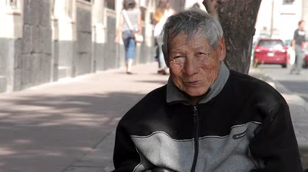 homeless : Mexico City, Mexico-August 2014: MEDIUM SHOT. Old man sitting in the sidewalk. In Mexico, the high rate of poverty make that many people have to live in the streets, included old people. Stock Footage