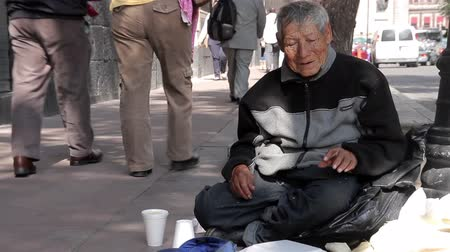 homeless : Mexico City, Mexico-August 2014: FULL SHOT. Old man sitting in the sidewalk. In Mexico, the high rate of poverty make that many people have to live in the streets, included old people.