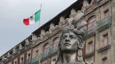 sas : Mexico City, Mexico-August 2014: MEDIUM SHOT-BLUR EFFECT. Moctezumas Statue. He was the last emperor of Tenochtitlan before the arrived and conquest of Mexico by the Spanish. Mexican flag waving.