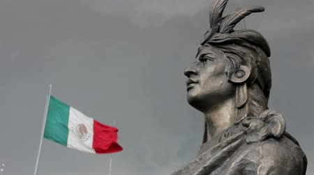 sas : Mexico City, Mexico-August 2014: MEDIUM SHOT. Moctezumas Statue. He was the last emperor of Tenochtitlan before the arrived and conquest of Mexico by the Spanish. Mexican flag waving.