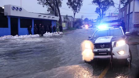 incapacidade : C. Izcalli, State of Mexico 06Sep17. Policemen gard an area affected by the flood, the water flows on the sewers due the flood by the collapse of the dam El Angulo during torrential rains. Stock Footage