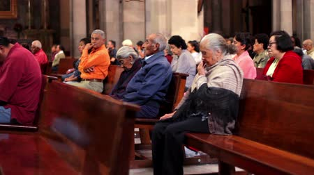 rahip : Toluca, Mex-CIRCA August 2017: Old people sitting on wooden benches praying inside the San Jose Cathedral during mass. Most mexicans profess the Catholic religion.