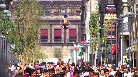 fazla : Mexico City, CIRCA June 2018 SLOW MOTION: Cheerleader jumps and makes an acrobatic movement in the air. Around her, a crowd walks in the street. Stok Video
