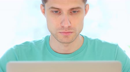 kapatmak : Young Man Working On Laptop in Office, Front View Close Up