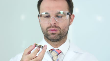 polovodič : Scientist in Protective Glasses Looking for Computer Chip