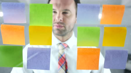 yapışkan : Man Working On Sticky Notes Attached on Glass in Office Stok Video
