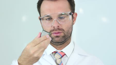 protective eyewear : Man in Protective Glasses Looking for Computer Chip Stock Footage
