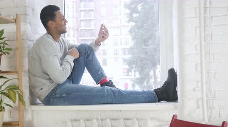 conferência : Video Chat on Smartphone by Arican Man Sitting at Window Stock Footage
