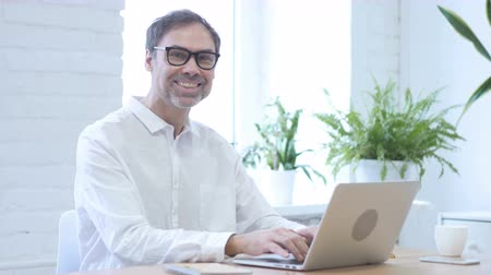 удовлетворения : Man Smiling While Looking at Camera at Work, Typing On Laptop Стоковые видеозаписи