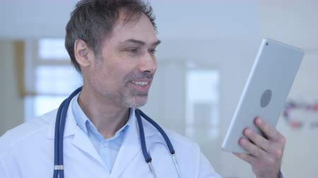 tab : Online Video Chat on Tablet by Doctor in Hospital Stock Footage