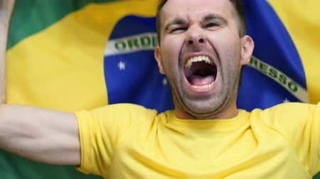 бразильский : Brazilian Fan Celebrates holding the flag of Brazil in Slow Motion