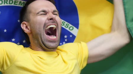 бразильский : Brazilian Fan Celebrating while holding the flag of Brazil in Slow Motion Стоковые видеозаписи