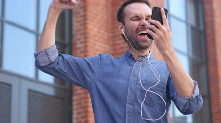 emin : Happy Dancing Casual Man Listening Music on Smartphone