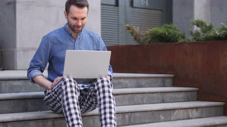 zeptat se : Online Video Chat on Laptop while Sitting on Stairs Outside Office