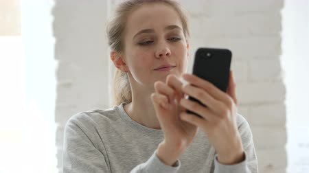 surfing the net : Young Woman Browsing on Smartphone in Loft Workplace