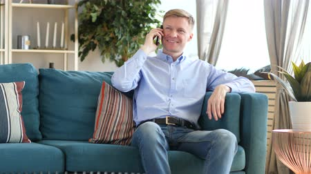 vytočit : Middle Aged Man Talking on Phone, Sitting on Couch