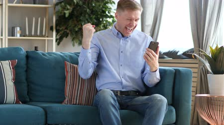 başarılı olmak : Middle Aged Man Excited for Success while Using Smartphone