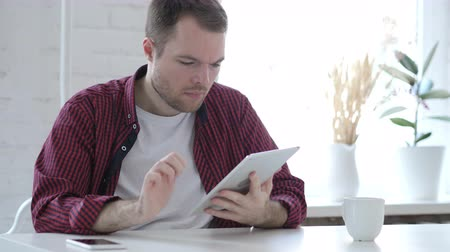 surfing the net : Young Man Browsing and Scrolling on Tablet