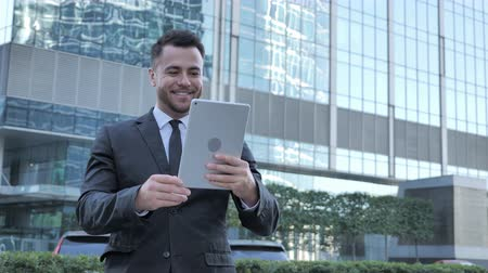 bankier : Walking Businessman Doing Online Video Chat on Tablet