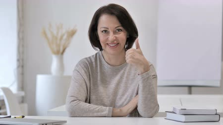 freelance work : Thumbs Up by Old Senior Woman Looking at Camera at Work