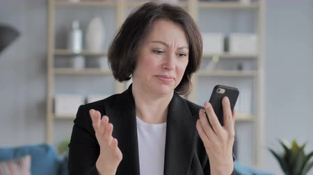 navegador : Old Businesswoman Reacting to Loss while Using Smartphone