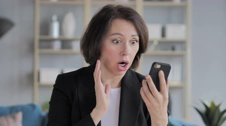 krutý : Old Businesswoman in Shock while Using Smartphone