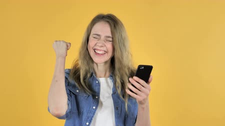 e mail address : Young Pretty Girl Excited for Success while Using Smartphone on Yellow Background
