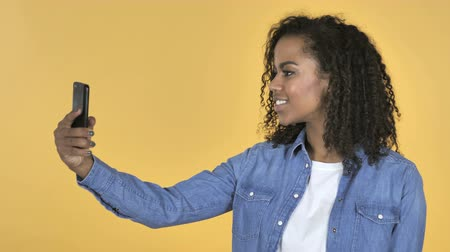 страница : African Girl Taking Selfie with Smartphone Isolated on Yellow Background