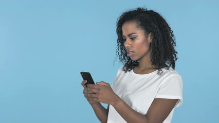 адрес : African Girl Browsing Smartphone Isolated on Blue Background Стоковые видеозаписи
