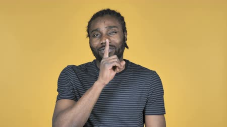 sessiz : Casual African Man Gesturing Silence, Finger on Lips, Yellow Background Stok Video