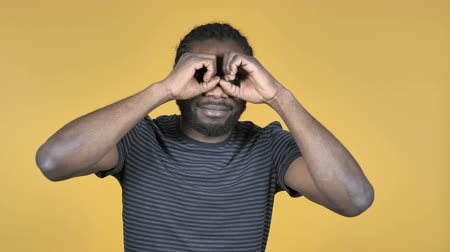 binocular : Casual African Man Searching with Handmade Binoculars Isolated on Yellow Background Stock Footage