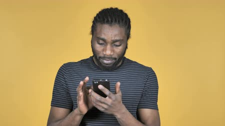 galhofeiro : Casual African Man Browsing Smartphone Isolated on Yellow Background