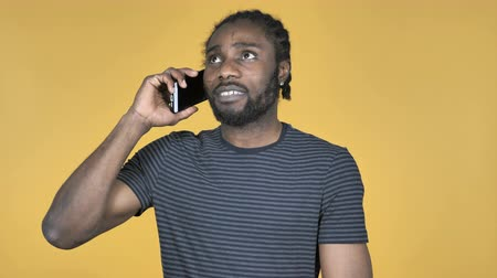 galhofeiro : Casual African Man Talking on Smartphone Isolated on Yellow Background Vídeos