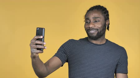 galhofeiro : Taking Selfie With Smartphone Isolated On Yellow Background