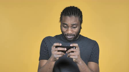 コミカル : Casual African Man Playing Game on Smartphone Isolated on Yellow Background
