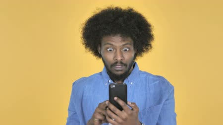 e mail address : Afro-American Man in Shock while Using Smartphone on Yellow Background