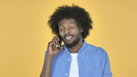 vytočit : Afro-American Man Talking on Smartphone on Yellow Background Dostupné videozáznamy