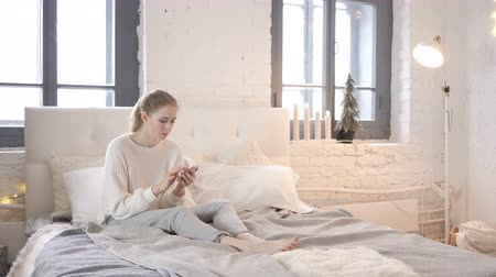 hazai room : Young Girl Using Smartphone while Sitting in Bed