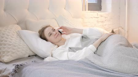 discar : Young Girl Talking on Phone while Laying in Bed