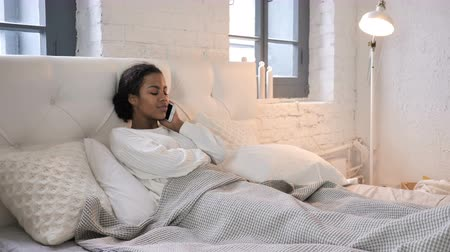 discar : Young African Girl Talking on Phone while Relaxing in Bed