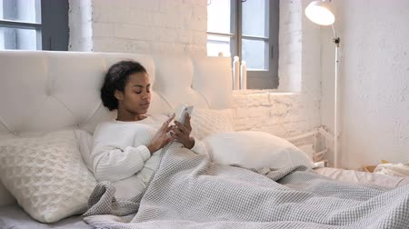 suceder : Young African Girl Celebrating Success while Using Smartphone in Bed Vídeos
