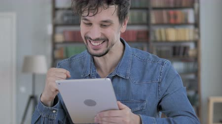 suceder : Excited Young Man Celebrating Success Using Tablet